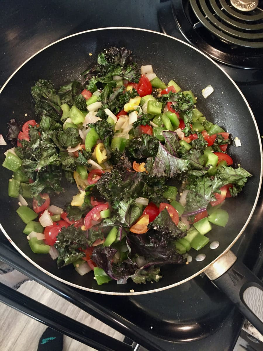 peppers, onions, tomatoes, red kale cooking in a pan