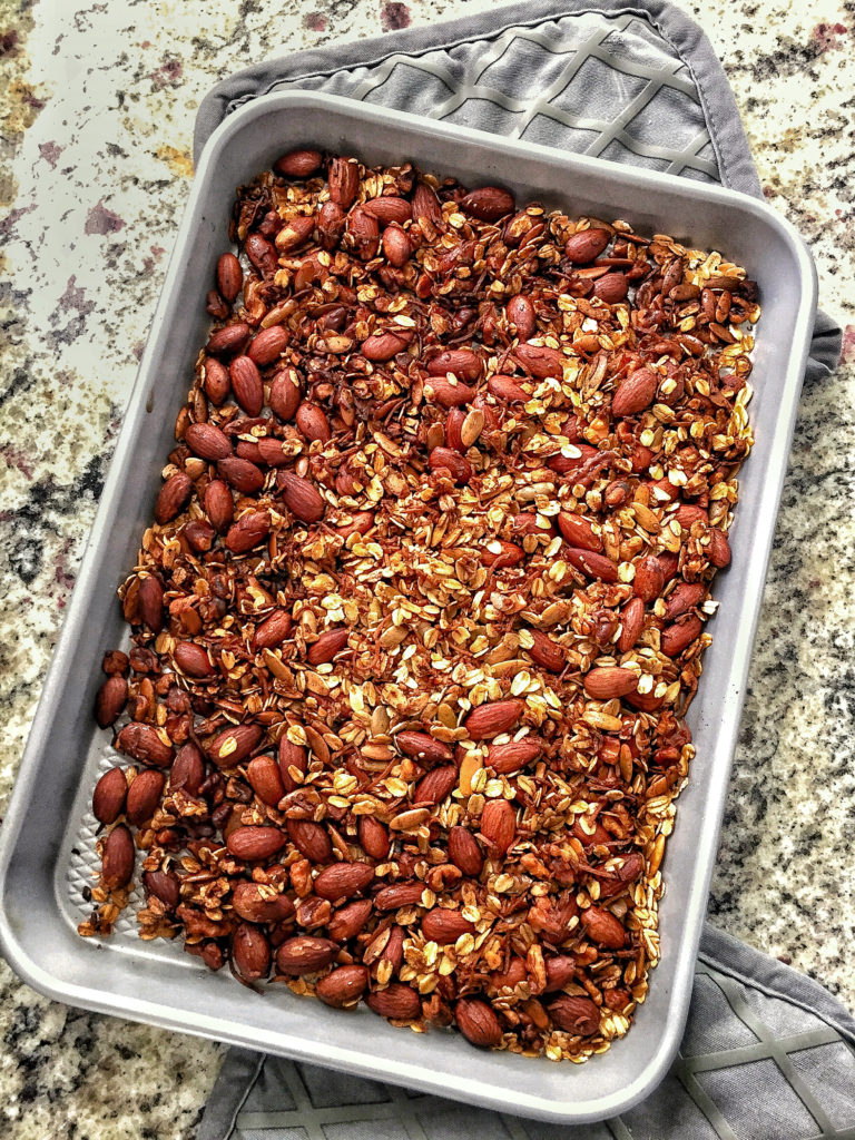 healthy homemade granola on a sheet pan with oven mitts