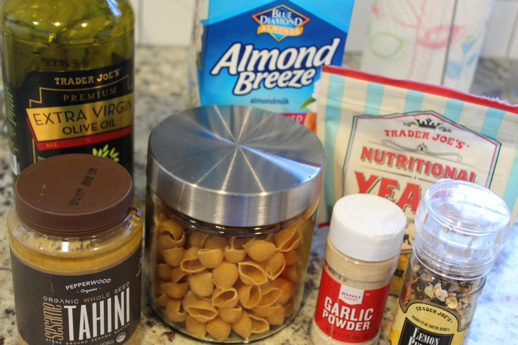ingredients for vegan alfredo pasta. olive oil, banza shells, tahini, almond milk, nutritional yeast, garlic powder, lemon pepper