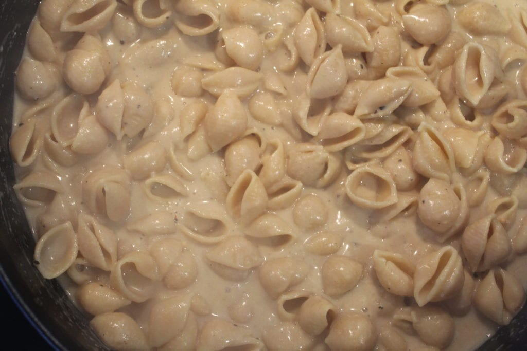 vegan alfredo pasta shells cooking on the stove
